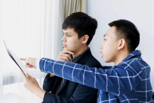 Geschäftspartner konzipieren zwei junge männliche produzenten, die ideen für die entwicklung eines modells eines neuen projekts diskutieren und ändern.