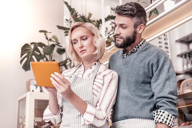 Geschäftspartner. nette junge leute, die auf den tablet-bildschirm schauen, während sie ihren zeitplan organisieren