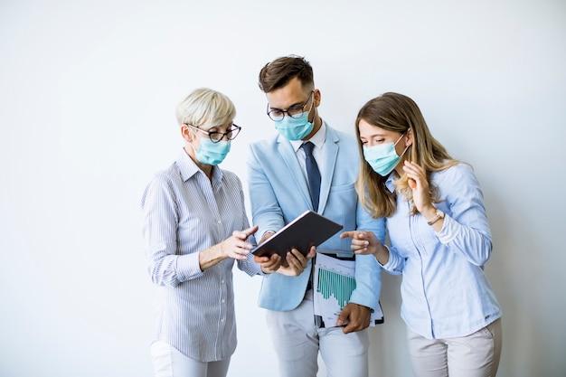 Geschäftspartner stehen und betrachten geschäftsergebnisse im büro, während sie gesichtsmasken als virenschutz tragen