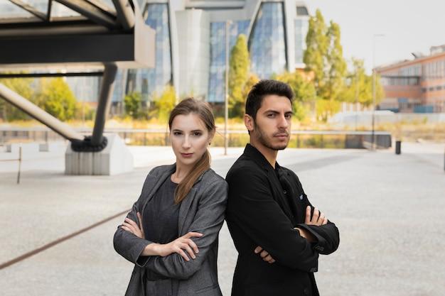 Geschäftspartner vor dem hintergrund eines bürogebäudes. sie sind zuversichtlich in sich und ihren geschäftlichen erfolg.