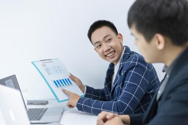 Geschäftspartnerkonzept ein junger geschäftsmann, der auf die gewinnzusammenfassung des letzten monats zeigt, die in dokumentformularen angezeigt wird.