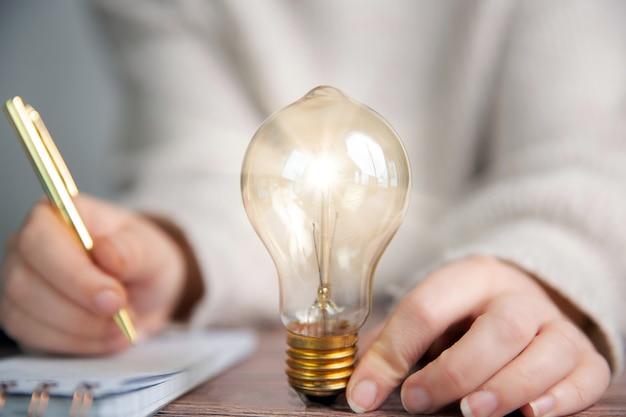 Geschäftsperson, der notizen, ideen, kreatives brainstorming mit leuchtender glühbirne schreibt,