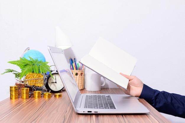 Geschäftsperson, die computer benutzt und buch liest