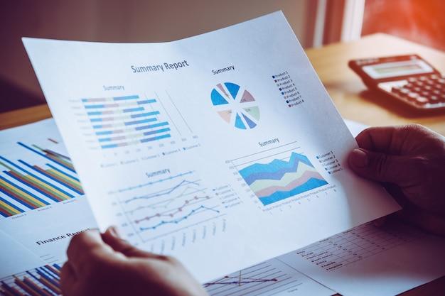 Geschäftsperson, die finanzstatistiken analysiert, die auf diagramm des umsatzes bei der diskussion über es auf hölzernem schreibtisch im büro angezeigt werden. gruppenunterstützungskonzept.
