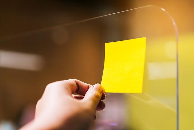Geschäftsperson, die haftnotiz auf plexiglasabscheider verwendet