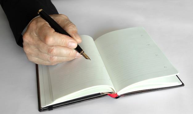 Geschäftsperson, die mit einem stift auf einem notizblock schreibt.
