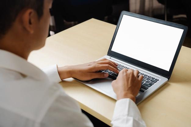 Geschäftsperson oder büroangestellter, der laptop-computer beim sitzen am schreibtisch verwendet.