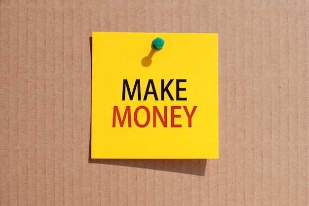 Geschäftsphrase - geld verdienen - auf gelbem quadratischem papier geschrieben und auf karton geheftet, konzept
