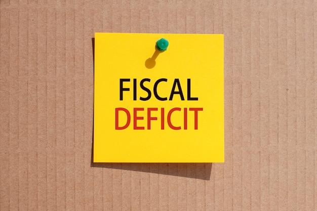 Geschäftsphrase - haushaltsdefizit - auf gelbem quadratischem papier geschrieben und auf karton geheftet, konzept
