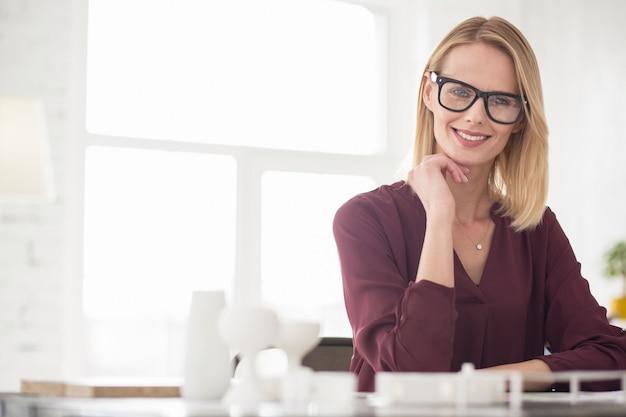 Geschäftsplan. erfreute charmante geschäftsfrau, die brille trägt, während gesicht berührt