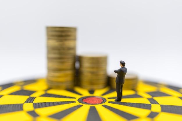 Geschäftsplanung, geld-, ziel- und zielabdeckungskonzept. miniaturfigur des geschäftsmannes stehen und suchen, um goldmünzen auf gelber und schwarzer dartscheibe zu stapeln.