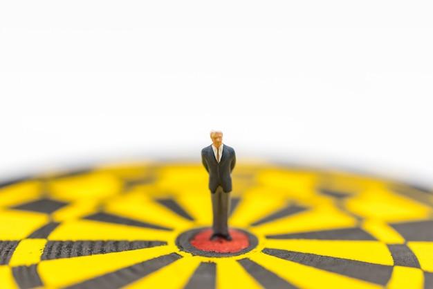Geschäftsplanung, ziel- und zielabdeckungskonzept. geschäftsmann-miniaturfigurmenschen, die auf rotem punktzentrum der gelben schwarzen dartscheibe stehen