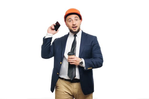 Geschäftsporträt des überraschten auftragnehmers und des entwicklers, der über telefon spricht. geschäftsmann im schutzhelm mit der tasse kaffee, die über weißem hintergrund steht. nachrichten- und kaffeebremskonzept