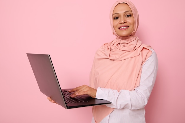 Geschäftsporträt einer erfolgreichen muslimischen programmiererin in rosa hijab, die vor einem farbigen hintergrund mit einem offenen laptop in den händen steht und text eingibt, lächelnd in die kamera schaut, raum kopieren