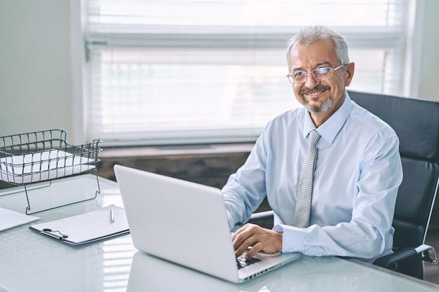 Geschäftsporträt eines älteren mannes, der an einem laptop arbeitet
