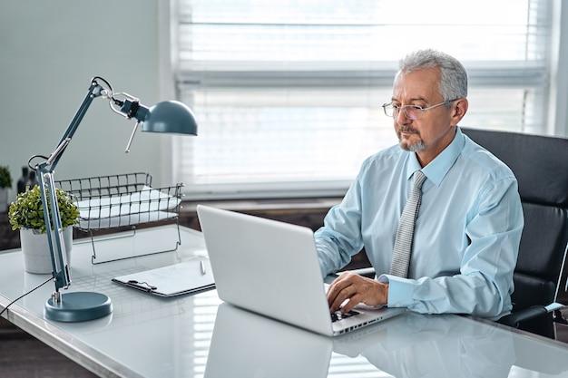 Geschäftsporträt eines älteren mannes. ein alter mann, der an einem laptop arbeitet. arbeit an der entfernung, freiberuflich.