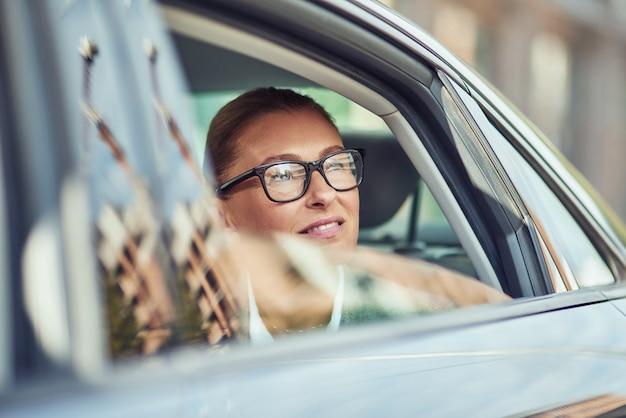 Geschäftsreise schöne geschäftsfrau mittleren alters mit brille, die aus einem autofenster schaut