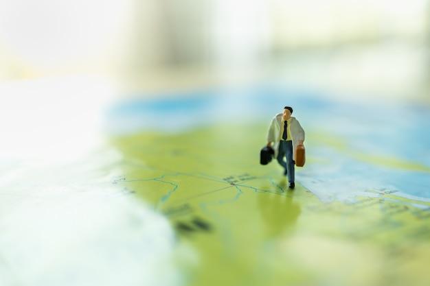 Geschäftsreise- und reisekonzept. schließen sie oben von der geschäftsmannminiaturzahl mit dem handtaschenkoffer, der auf bunter weltkarte läuft