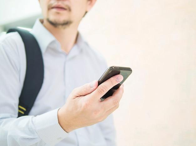 Geschäftsreisender, der handy während seiner reise am flughafenterminal verwendet