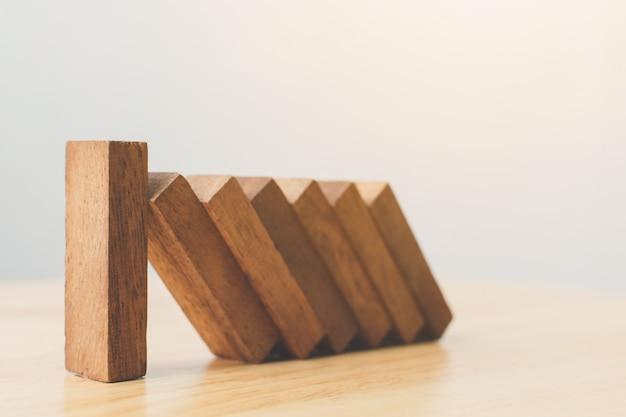 Geschäftsrisikomanagement-konzepte. holzklotzhalt, der von anderen stücken dominoeffekt fällt.