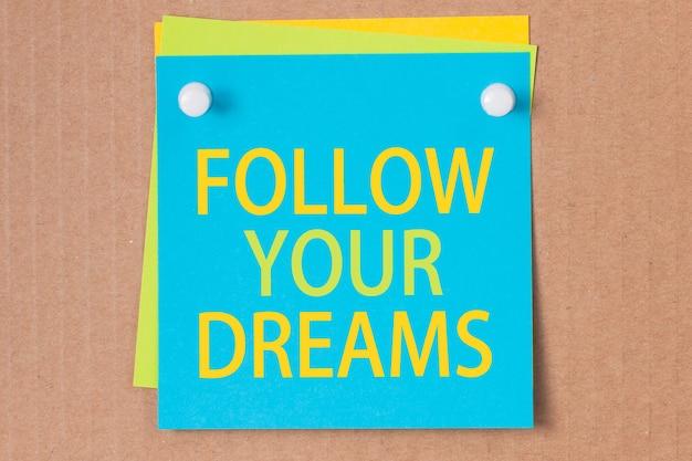 Geschäftssatz - folgen sie ihren träumen - geschrieben auf blauem quadratischem aufkleber und festgesteckt auf pappe