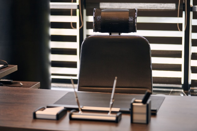 Geschäftsstelle am arbeitsplatz. arbeitsplatz für chef, chef oder andere angestellte. tisch und bequemer stuhl. licht durch die halb offenen jalousien