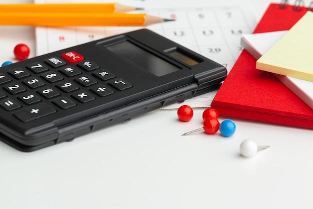 Geschäftsstillleben mit taschenrechner auf tabelle im büro.