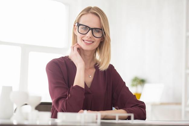 Geschäftsstrategie. lustige fröhliche geschäftsfrau, die brille trägt, während sie zur kamera grinst