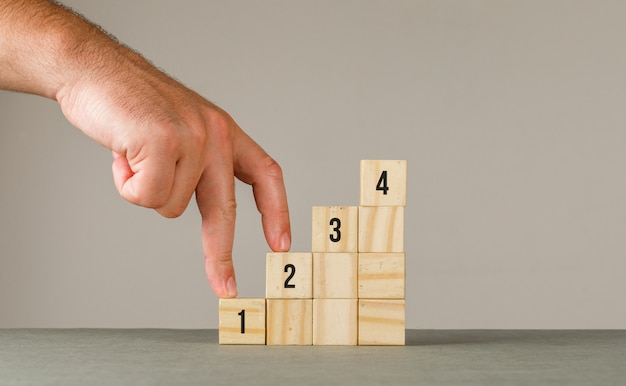 Geschäftsstrategiekonzept auf grauer und weißer wandseitenansicht. mann, der finger auf stufentreppe legt.
