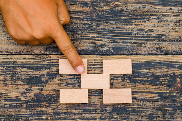 Geschäftsstrategiekonzept auf hölzernem hintergrund flach lag. finger auf holzblock.