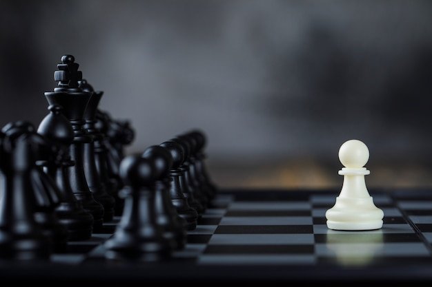 Geschäftsstrategiekonzept mit figuren auf schachbrett auf nebel- und holztischseitenansicht.