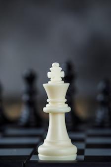 Geschäftsstrategiekonzept mit figuren auf schachbrett auf unscharfer und hölzerner tischnahaufnahme.