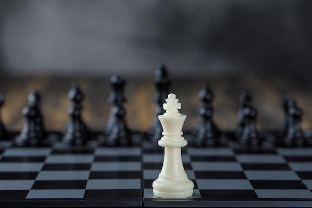 Geschäftsstrategiekonzept mit figuren auf schachbrett auf unscharfer und hölzerner tischseitenansicht.