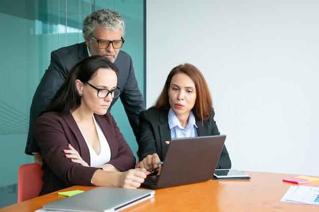 Geschäftsteam beobachtet präsentation auf laptop, zeigt auf anzeige, diskutiert details