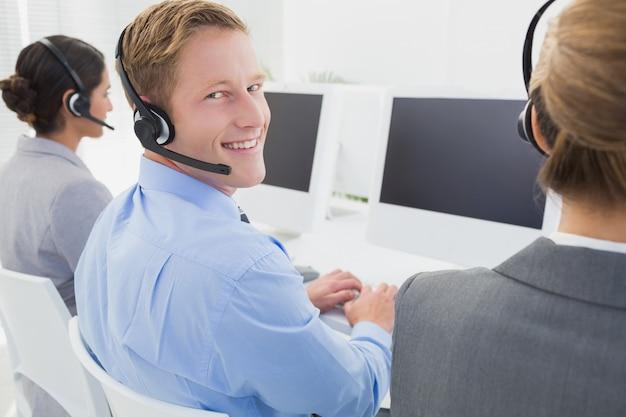 Geschäftsteam, das an computern arbeitet und kopfhörer trägt