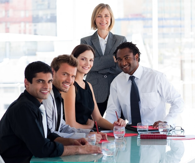 Geschäftsteam, das an der kamera im büro lächelt