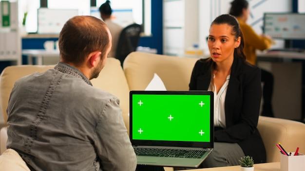 Geschäftsteam, das auf der couch sitzt und finanzstatistiken analysiert, laptop mit grünem bildschirm hält, während verschiedenes team am hintergrund arbeitet. multiethnische mitarbeiter planen projekt auf chroma-key-display