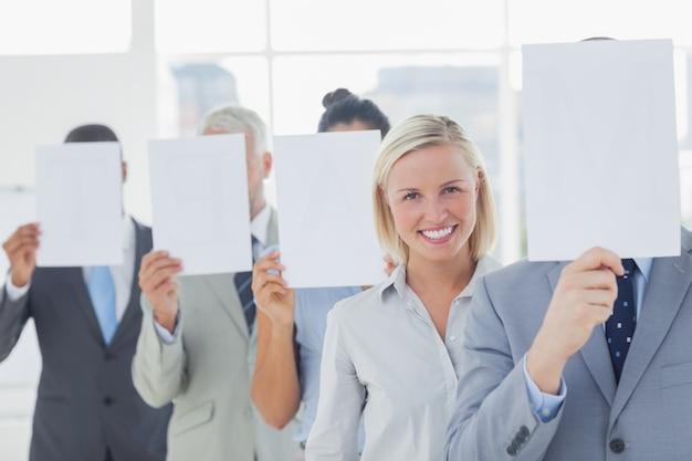 Geschäftsteam, das gesicht mit weißbuch außer einer frau abdeckt