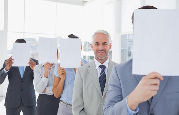 Geschäftsteam, das gesicht mit weißbuch mit ausnahme von einem bedeckt