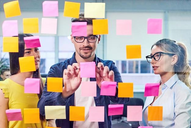 Geschäftsteam, das ideen auf aufklebern im büro bespricht