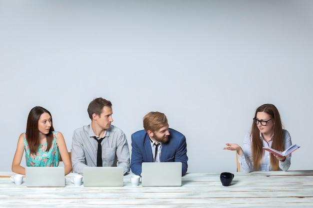 Geschäftsteam, das im büro auf hellgrauem hintergrund zusammenarbeitet. alle arbeiten an laptops. chef liest notizbuch. copyspace-bild
