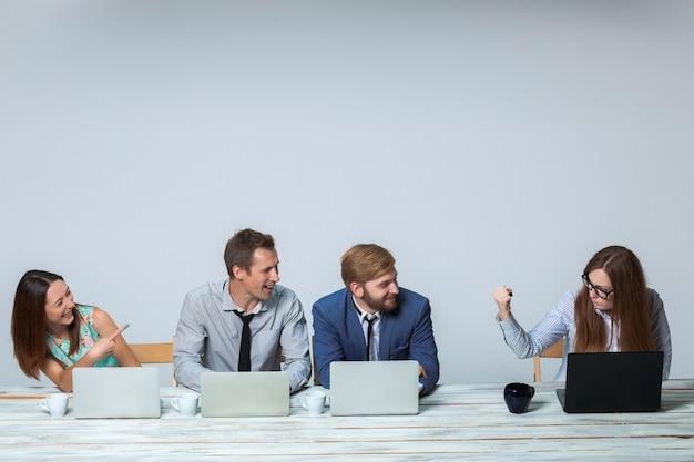 Geschäftsteam, das im büro auf hellgrauem hintergrund zusammenarbeitet. schulleiterin droht, andere lachen. copyspace-bild