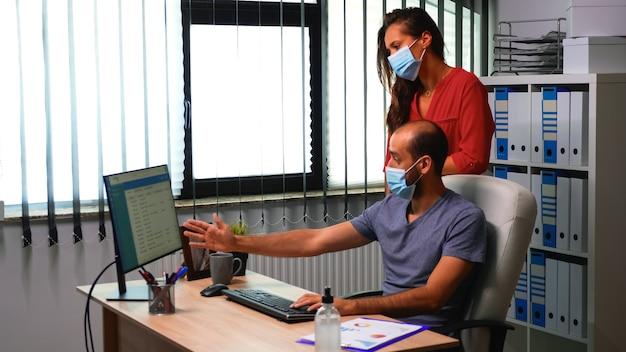 Geschäftsteam, das im neuen normalen büroraum mit schutzmaske arbeitet. mitarbeiter im modernen arbeitsbereich eines unternehmens, die auf der computertastatur tippen und auf den desktop zeigen, um die kundenliste zu analysieren
