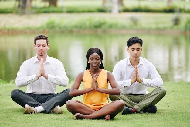Geschäftsteam, das im park meditiert