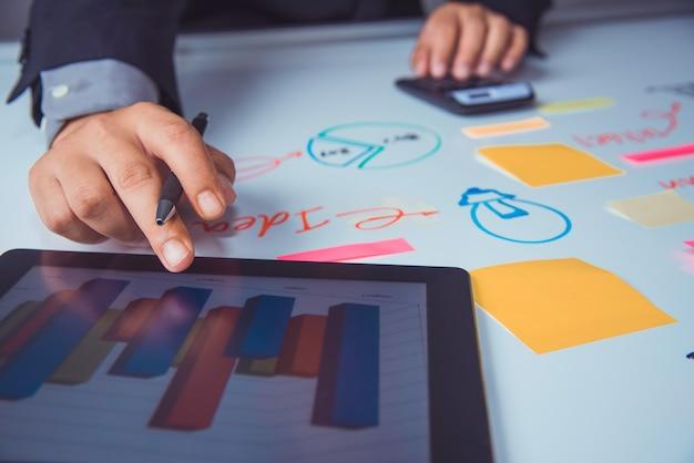 Geschäftsteam, das mit laptop und smartphone im büro des offenen raumes arbeitet. sitzungsbericht in bearbeitung