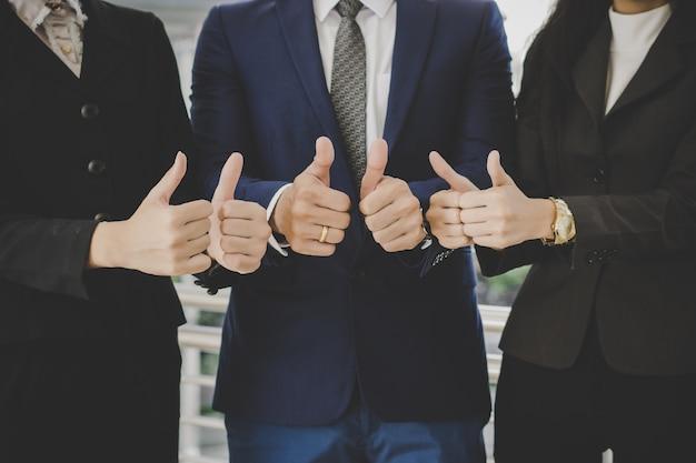 Geschäftsteam, das vor erfolgreichem geschäft des büros mit dem zeigen von daumen steht