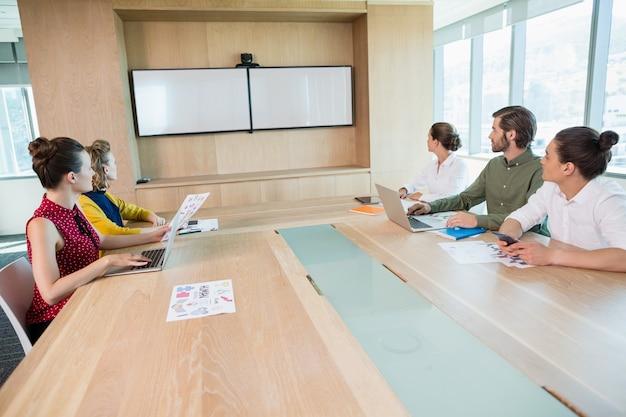 Geschäftsteam, das weißen bildschirm im besprechungsraum betrachtet
