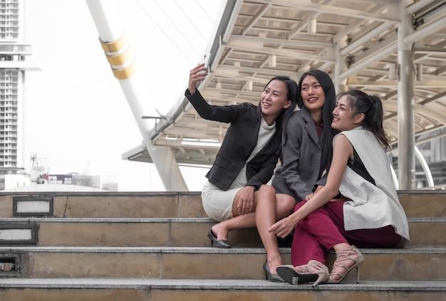 Geschäftsteam der jungen frau, das draußen das nehmen eines selfie einstellt