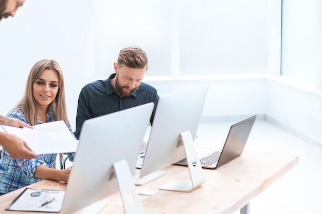 Geschäftsteam diskutiert arbeitsdokumente in einem hellen büro. foto mit textfreiraum