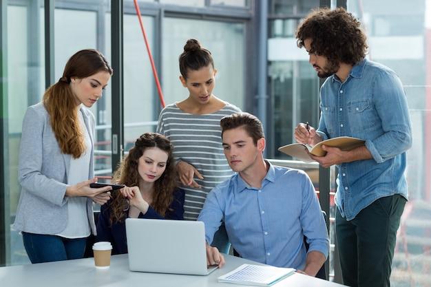 Geschäftsteam diskutiert über laptop in besprechung